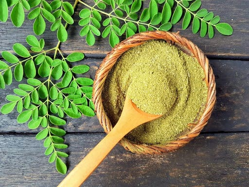 Moringa powder in a basket with a wooden spoon, with moringa leaves next to it.