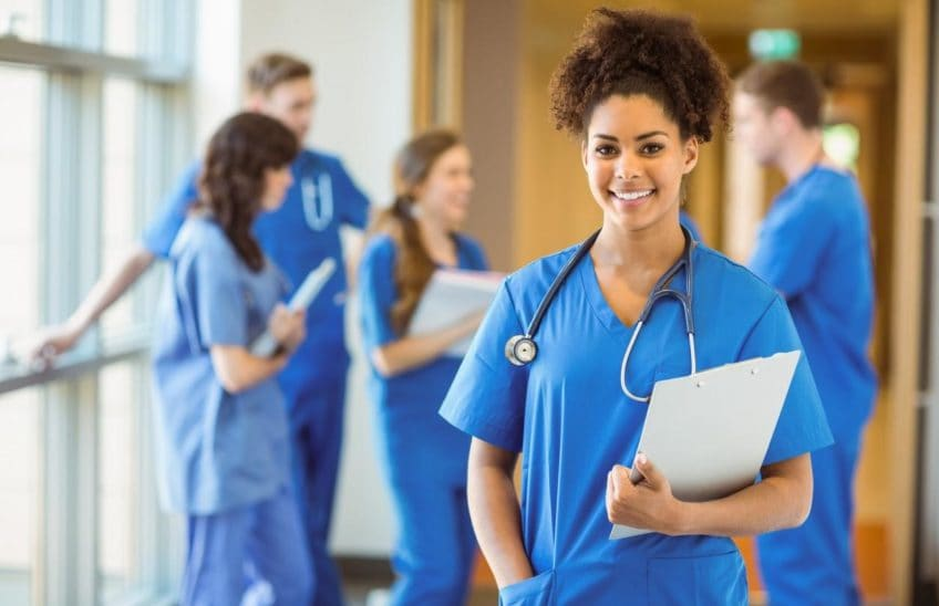 Woman in scrubs holding a clipboard with 4 people in scrubs in the background.