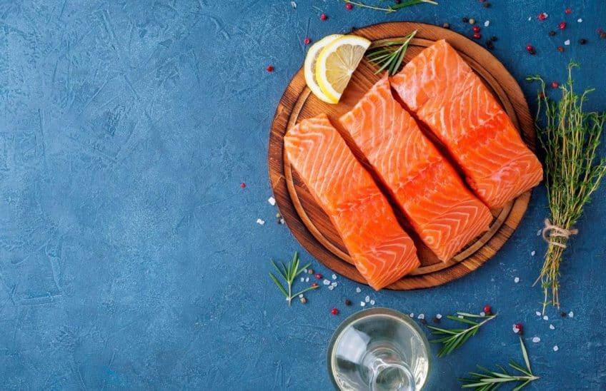 Raw salmon filets on a round wooden board next to herbs and a bottle of oil against a blue surface