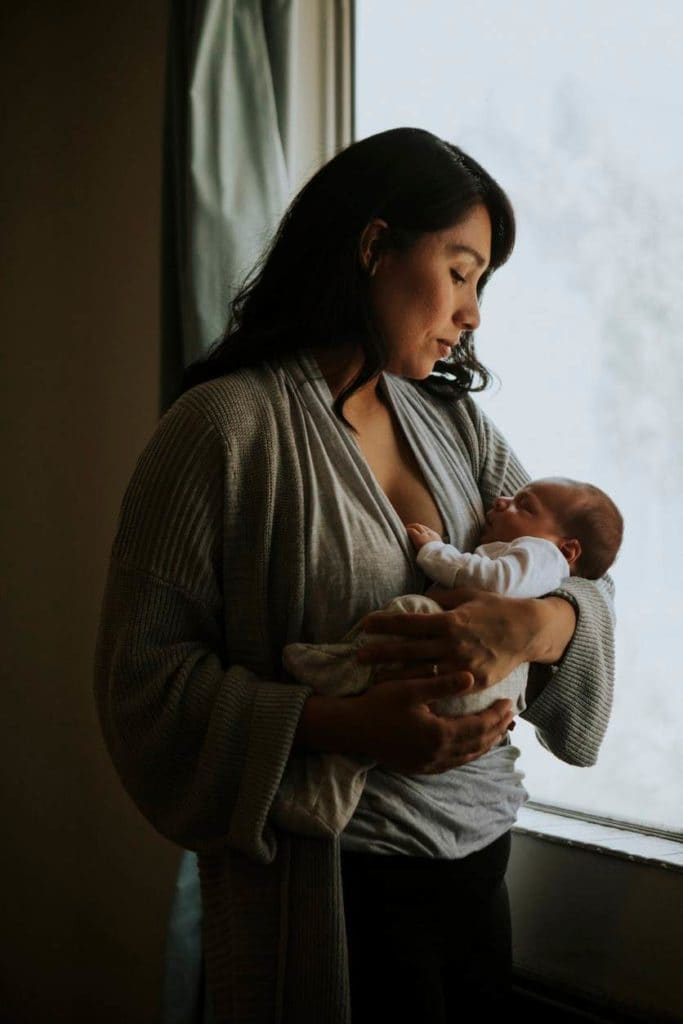 Woman holding a baby inside a dark room.
