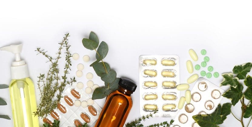 An array of fresh herbs, pills, and tinctures lying on a white surface.