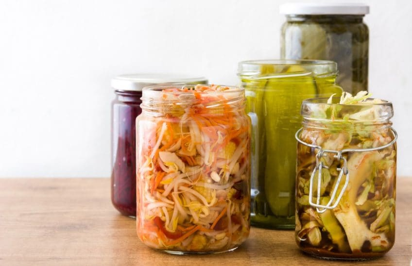 5 clear glass jars containing different fermented vegetables.