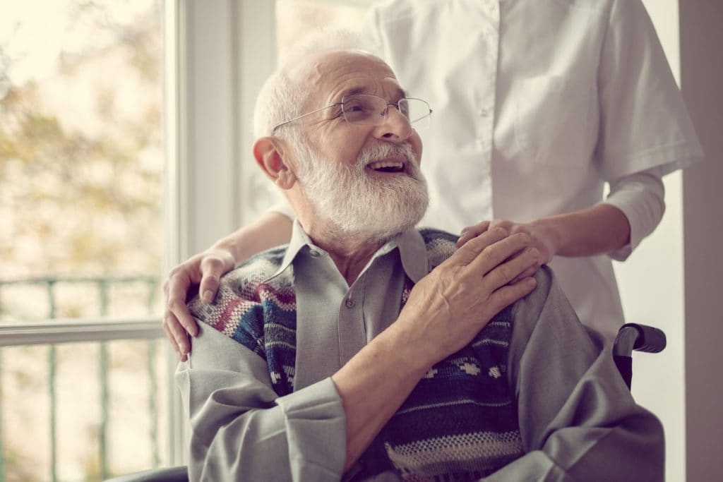 Elderly man seated in a wheelchair smiling and touching his nurse's hand.