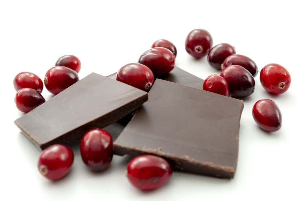 Fresh cranberries and pieces of dark chocolate on a white surface.