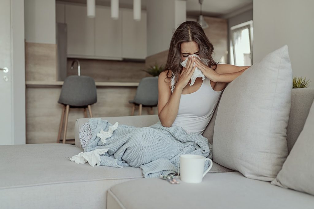 Woman sitting on a couch under a blanket and sneezing into a tissue.