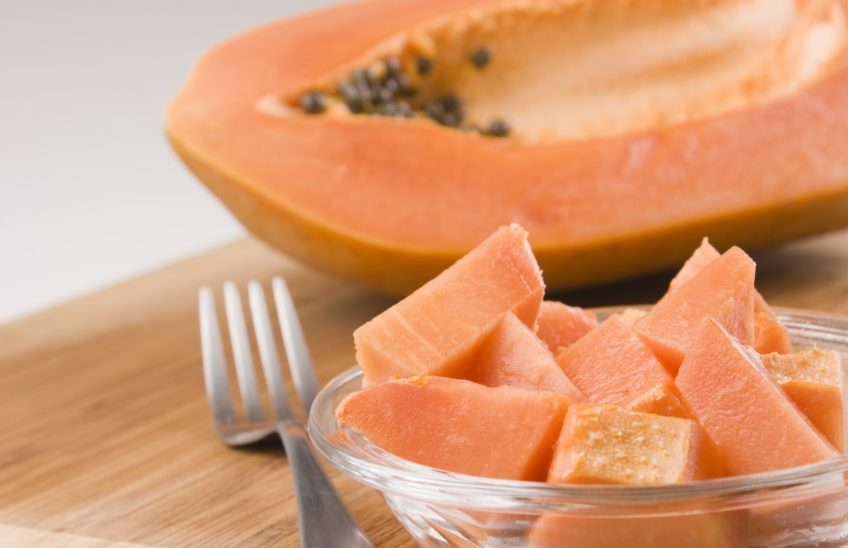 chunks of papaya in a bowl in front of a half papaya on a wooden cutting board.