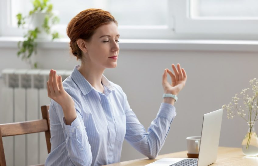 Woman meditating while sitting at a desk in front of a laptop.