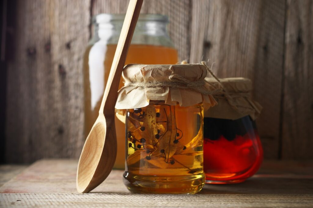 Wooden spoon leaning on a jar of honey with herbs in it.