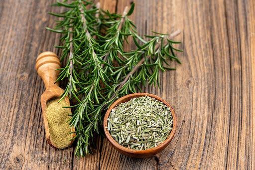 Sprigs of fresh rosemary, a bowl of dried rosemary, and a wooden scoop of ground rosemary.