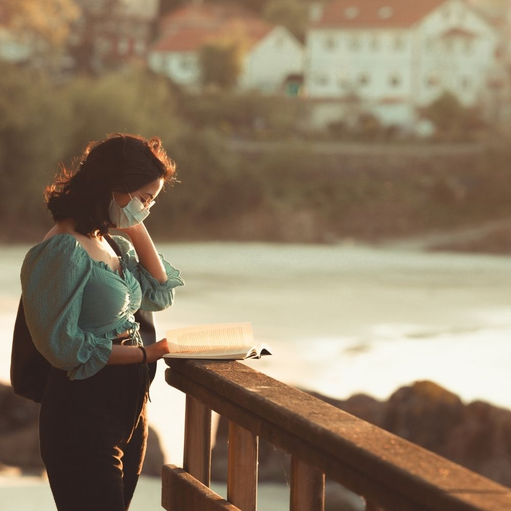 Woman Reading on A Railing